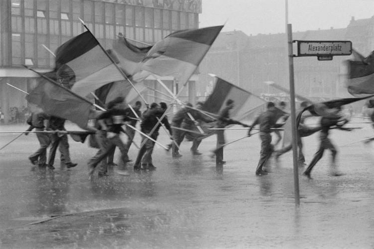 Молодые люди с немецкими флагами во время ливня на Александрплатц в Восточном Берлине винтаж, германия, люди, фото