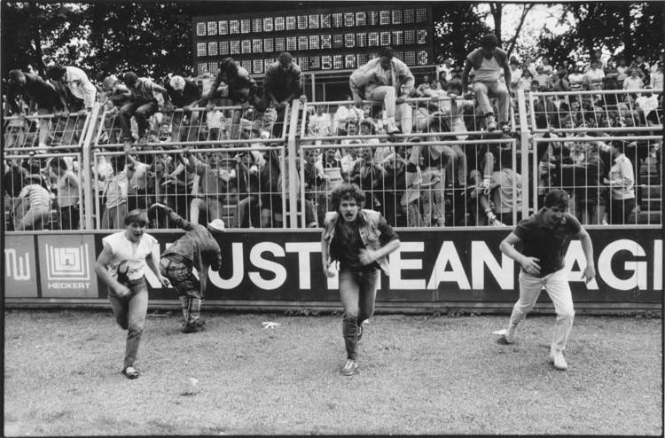 Хулиганы перескочили через забор и выбежали на поле по окончании напряженного футбольного матча винтаж, германия, люди, фото