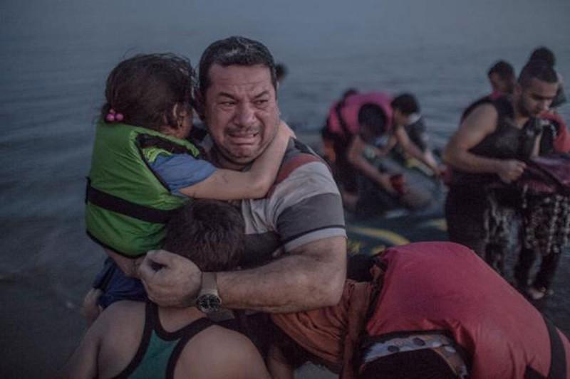 15. Сириец Лаит Маджид, обнимающий свою дочь и сына, добравшийся из Турции на греческий остров Кос беженцы, мир, помощь
