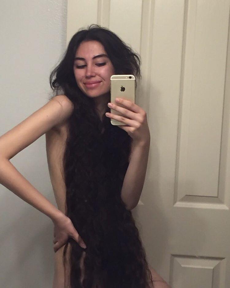 Модель, у которой такие длинные волосы, что она может носить их вместо футболки волосы, девушка