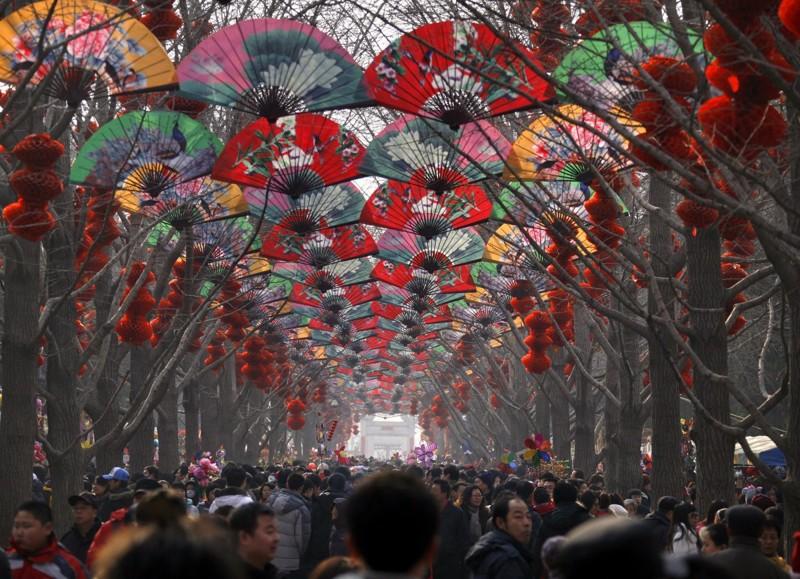 Толпы прогуливаются под рядами деревьев, украшенных веерами и красными фонарями во время фестиваля в честь китайского Нового года в Пекине. китай, люди, население
