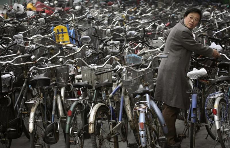 Женщина забирает свой велосипед с велопарковки у станции метро в Пекине. китай, люди, население