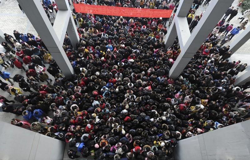 Студенты у входа в учебный корпус перед трехдневным экзаменом в аспирантуру в Хэфэе, провинция Аньхой. В 2013 году на этот экзамен записалось рекордное число студентов — 1,8 миллиона человек. китай, люди, население
