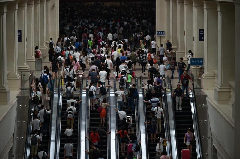 Пассажиры медленно пробираются к эскалаторам, чтобы спуститься на платформы. китай, люди, население