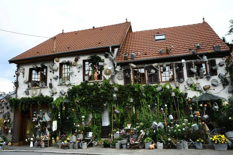 дом украшенный садовыми лейками