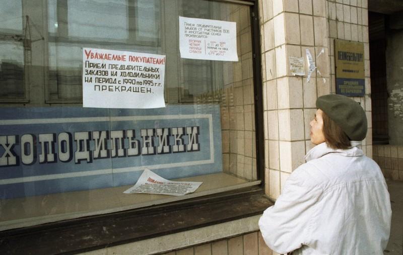 Женщина читает объявление в витрине магазина бытовой техники об отсутствии в продаже холодильников во время дефицита товаров в начале 90-х годов в СССР дефицит, люди, мечта