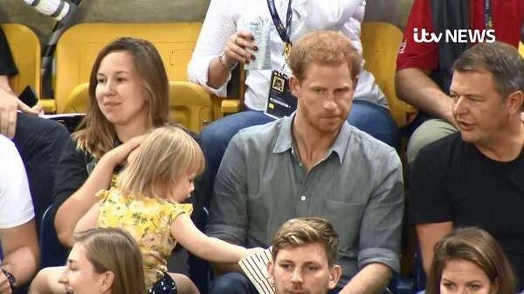 Получилась уморительная сценка. Сначала девочка несколько раз залезла рукой в кулёк с попкорном, который его королевское высочество держал в руках. При этом сам принц был настолько увлечён разговором со своим соседом, что ничего не замечал воровство, дети, милота, попкорн, прикол, принц, принц гарри, юмор