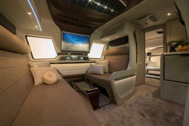 Дверь по левому борту (руль у автомобиля справа) открывает доступ в гостиную со столиком, плоским телеэкраном, а также диваном и креслом. авто, автомобили, дом на колесах, кемпер, микроавтобус, офис на колесах