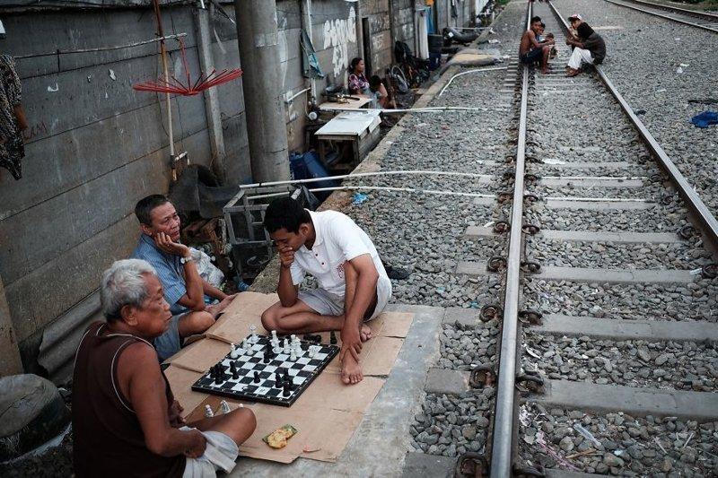6. Мужчины играют в шахматы на земле рядом с железнодорожными путями бедность, джакарта, железная дорога, индонезия, нищета, репортаж, трущобы