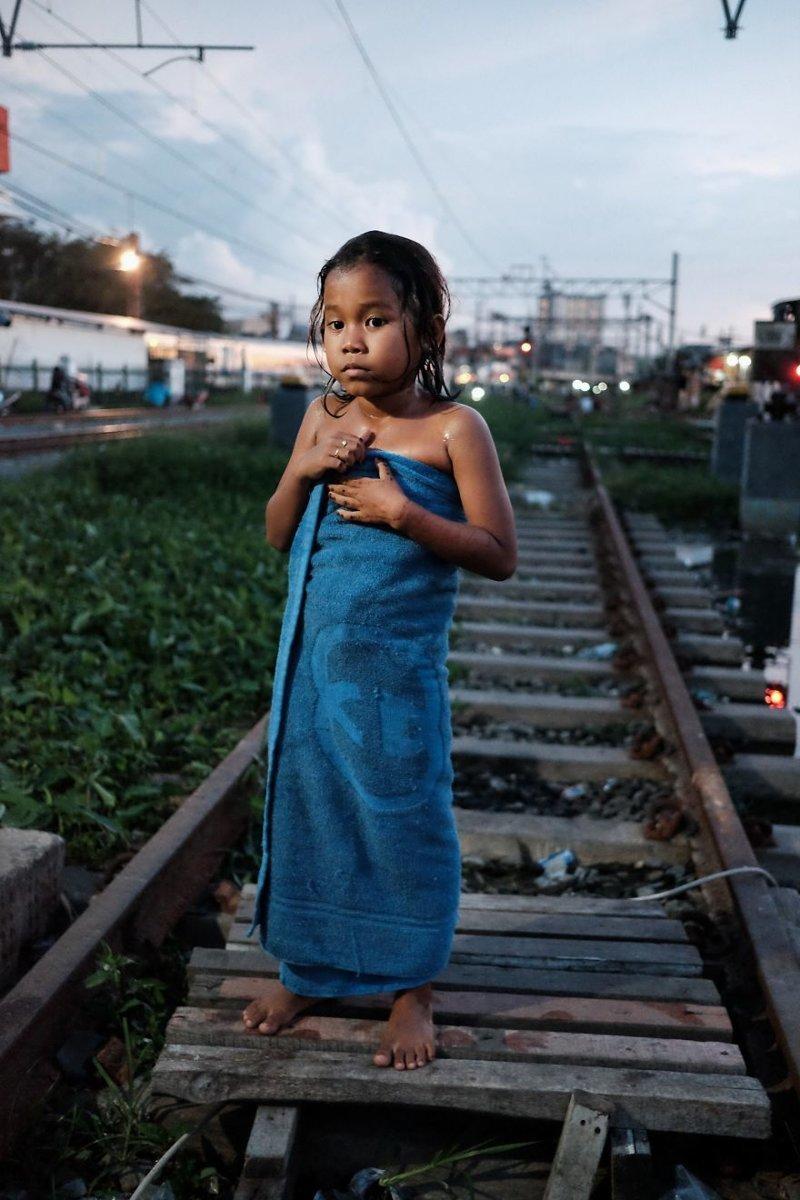 3. Маленькая девочка сушится в полотенце после душа бедность, джакарта, железная дорога, индонезия, нищета, репортаж, трущобы