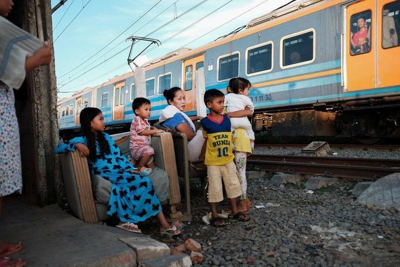22. Семья наблюдает за проходящим мимо их дома поездом бедность, джакарта, железная дорога, индонезия, нищета, репортаж, трущобы