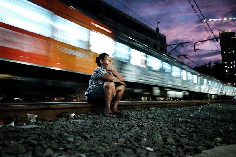 4. Женщина отдыхает, расположившись на рельсах, в то время как всего в паре метров от нее проносится поезд бедность, джакарта, железная дорога, индонезия, нищета, репортаж, трущобы