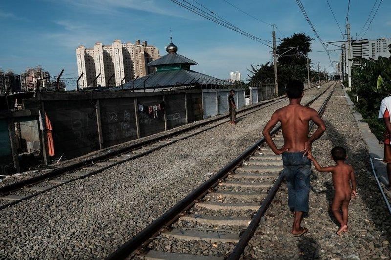 23. Отец с сыном прогуливаются вдоль действующей железной дороги бедность, джакарта, железная дорога, индонезия, нищета, репортаж, трущобы