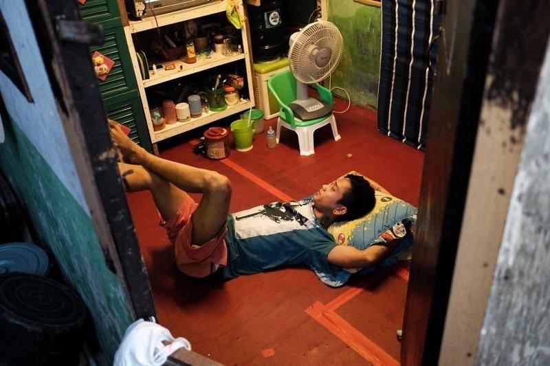 20. Юноша отдыхает в своем скромном жилище бедность, джакарта, железная дорога, индонезия, нищета, репортаж, трущобы