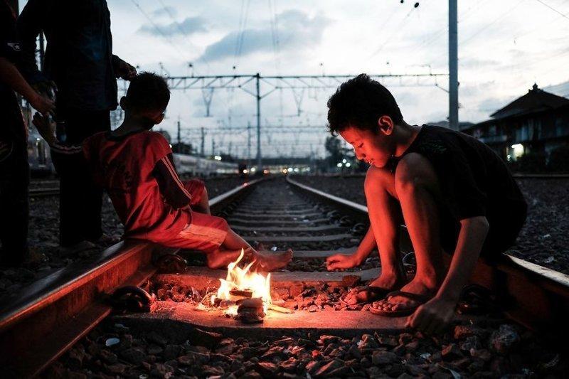 2. Дети играют с огнем на действующих железнодорожных путях в трущобном районе недалеко от станции Jakarta Kota. Другой площадки для игр у них нет бедность, джакарта, железная дорога, индонезия, нищета, репортаж, трущобы