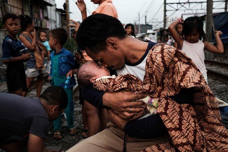 10. Джонатан держит на руках свою дочь после возвращения с работы бедность, джакарта, железная дорога, индонезия, нищета, репортаж, трущобы