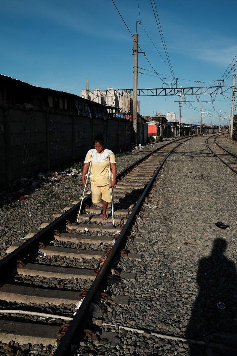 13. Женщина с одной ноги идет на костылях прямо по шпалам бедность, джакарта, железная дорога, индонезия, нищета, репортаж, трущобы