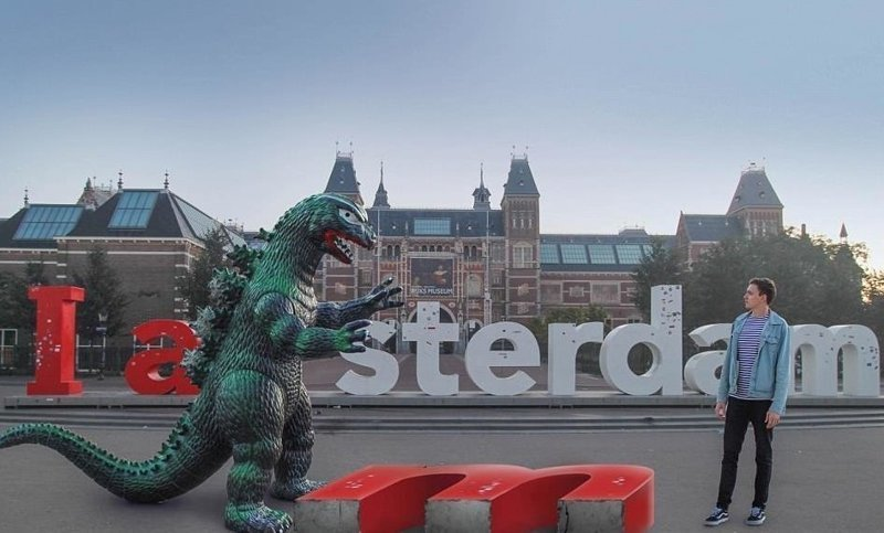 Монстр в Амстердаме Райан Годзиллинг, дино-путешественник, динозавр, на фоне памятников, необычно, оригинально, фото, фотографии