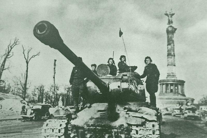 Советские танкисты на броне тяжелого танка ИС-2 у колонны Победы в Берлине.  Справа — колонна танков Т-34-85. Бронетехника СССР, Великая Отечественная  война, история