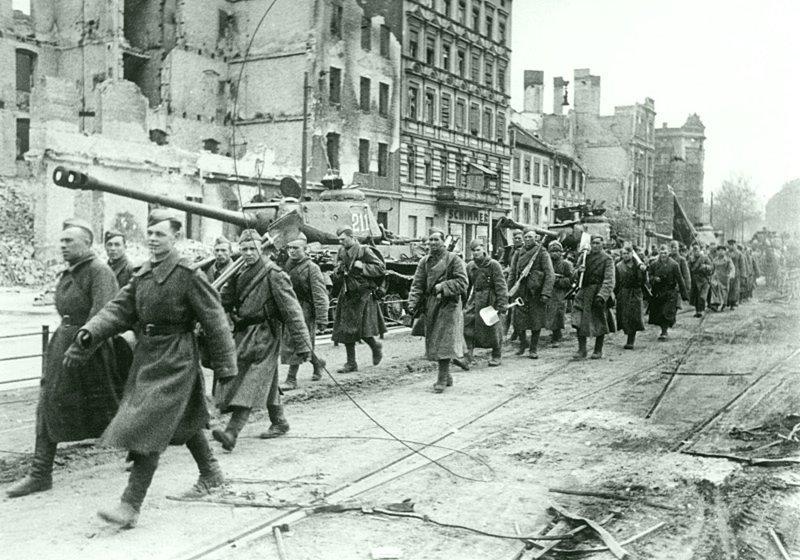 Советские бойцы с красным знаменем проходят возле колонны танков ИС-2 на улице Берлина. Германия, апрель-май 1945. Бронетехника СССР, Великая Отечественная  война, история