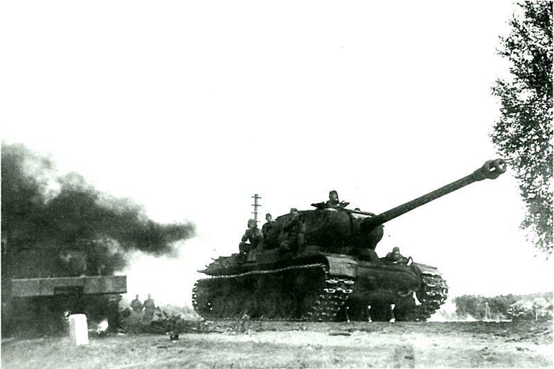 Танк ИС-2 с десантом на борту движется по Рижскому шоссе. Машина ранних выпусков с дульным тормозом немецкого типа. На обочине дороги разбитый и сгоревший грузовик Studebaker US6. сентябрь-октябрь 1944  Бронетехника СССР, Великая Отечественная  война, история