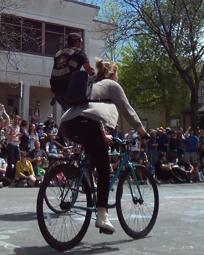Кажется, что велосипедистка везет на спине какого-то малыша. Но на самом деле, он не малыш и едет сам. Присмотритесь и убедитесь! двусмысленность, истории с подвохом, необычно, неоднозначно, оптические иллюзии, фото, фотография, что это было