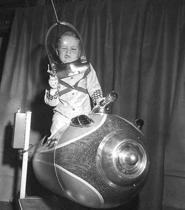 Космический рейнджер. Ребенок играл на космическом корабле, управляемом монеткой, на Американской ярмарке игрушек в 1953 году. история, черно-белая фотография, юмор
