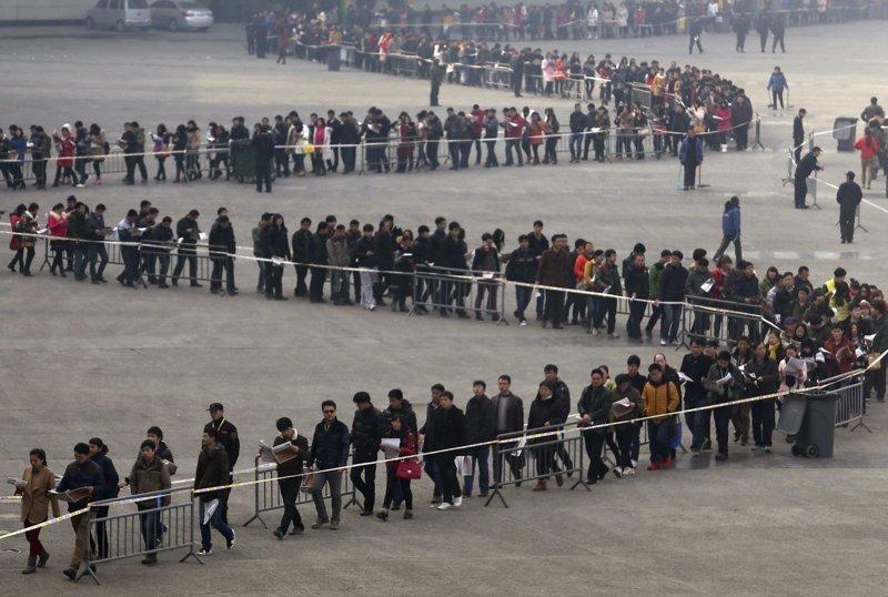 9. Студенты на ярмарке вакансий в 2014 году в городе Чжэнчжоу (провинция Хэнань). Всего ее посетило примерно 50 тысяч человек. китай, личное пространство, перенаселенность, повседневность, толпа, фото