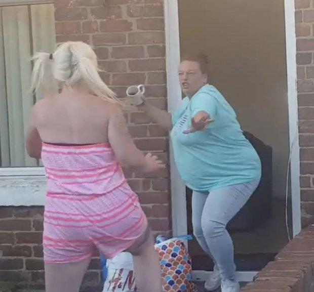 """Как истинная британка, дама в голубой футболке спешит """"угостить"""" противницу чашкой чая великобритания, драка, женщина, кадр, потасовка, ссора, улица"""