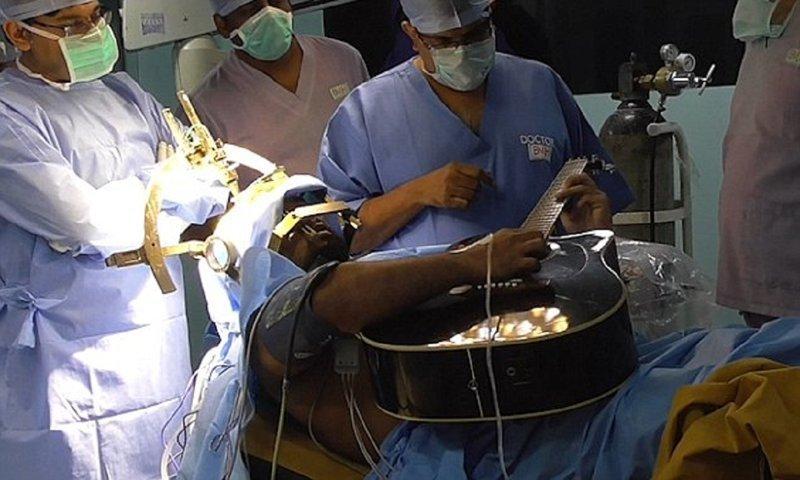 Пациент играет на гитаре во время операции на мозге Бангалор, дистония гитариста, индия, лечение, музыка без перерыва, необычная операция, странный пациент, фокальная дистония