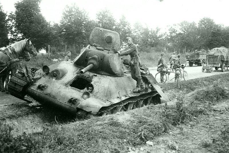 Немецкий солдат позирует на танке Т-34 подбитом на дороге в районе Дубно Великая Отечественная  война, СССР, история