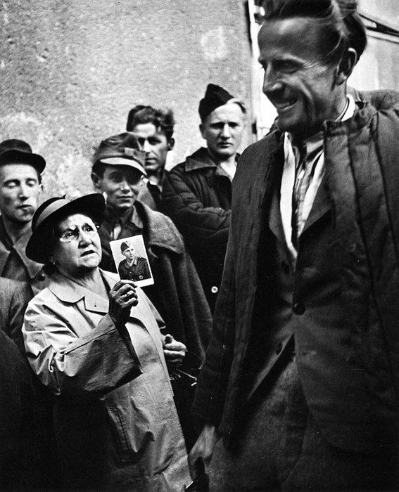 16. Мать показывает фотографию своего сына освобожденному заключенному после окончания Второй Мировой Войны война, история, память