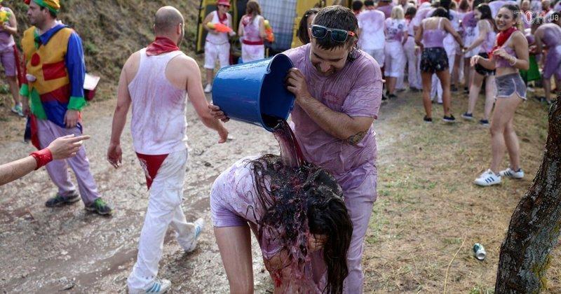 Для обливания люди используют различные предметы - от бурдюков до ковшей и ведер Фестиваль, в мире, вино, испания, люди, праздник