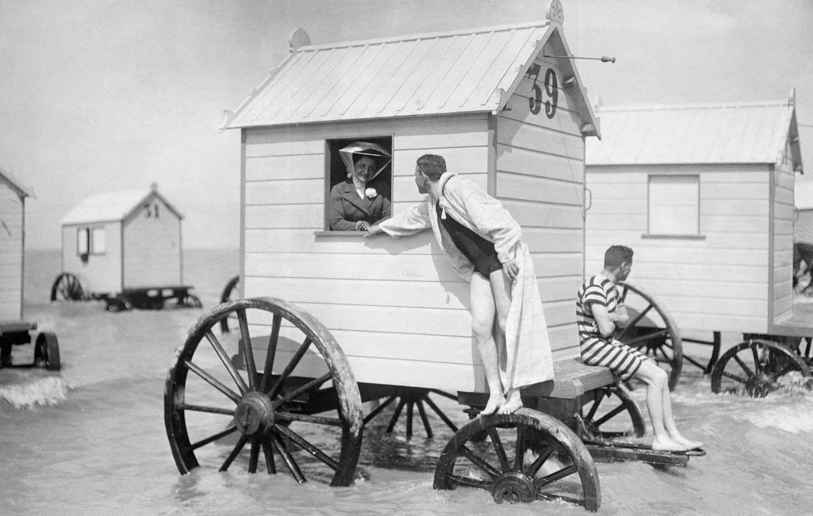 Отдыхающие наслаждаются водой из своего вагончика, примерно 1910 г. 100 лет назад, 20 век, архивные снимки, архивные фотографии, пляж, пляжный отдых, черно-белые фотографии, чёрно-белые фото
