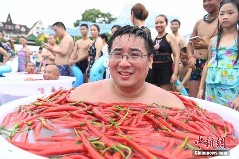 Большое количество людей собралось в южной китайской провинции Хунань, чтобы не только поучаствовать в соревновании по поеданию перца на скорость, но и искупаться в огромных ваннах, наполненных этим жгучим плодом интересное, китай, острота, перец, прикол, соревнования, туризм