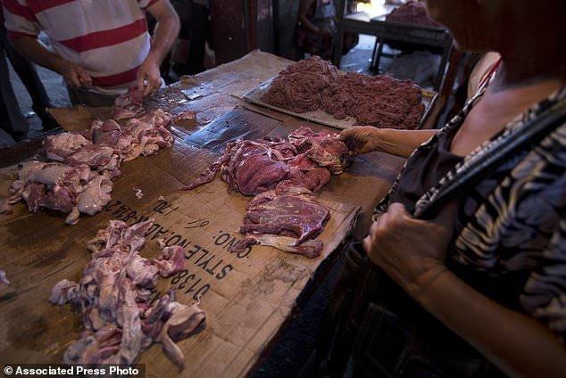 Покупательница рассматривает испорченное мясо ynews, венесуэла, кризис, рецессия, тухлятина, экономика дефолт, экономический кризис, южная америка