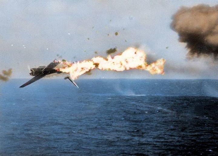 Японский палубный торпедоносец B5N разрушается в результате попадания 5-дюймового снаряда с борта авианосца «Йорктаун». 25 октября 1944 г. (в оригинале фото чёрно-белое) Великая отечественая война, архивные фотографии, вторая мировая война