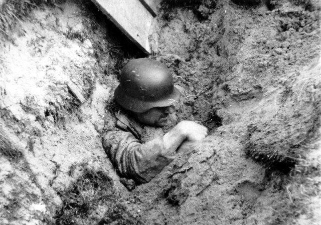 Немецкий солдат пытается выбраться из засыпанного близким разрывом окопа Великая отечественая война, архивные фотографии, вторая мировая война