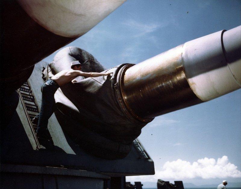 Матрос из состава экипажа американского линкора «Миссури» поправляет кожух на главном калибре. Август 1944 г. Великая отечественая война, архивные фотографии, вторая мировая война