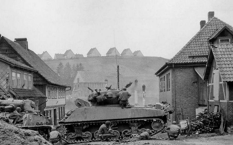 Солдаты 1-й пехотной дивизии укрываются от огня не обнаруженного немецкого снайпера за танками M4A3 «Шерман» 745-го танкового батальона армии США в Санкт-Андреасберге, Германия Великая отечественая война, архивные фотографии, вторая мировая война