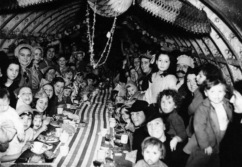 21. Мирные жители Лондона празднуют Рождество в бомбоубежище, 25 декабря 1940 года