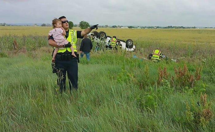 Полицейский отвлекает девочку, пока ее погибшего отца достают из машины