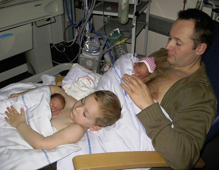 Старший сын помогает отцу держать своих недоношенных братиков