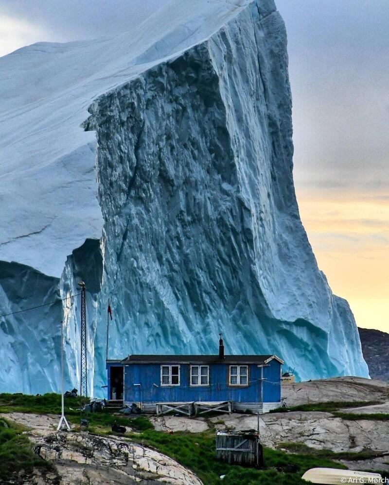 16. Огромный айсберг проплывает мимо домика в Гренландии